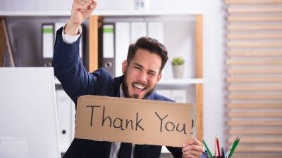 Homem  segurando placa escrito obrigado em inglês, com um dos braços levantado, comemorando