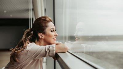 Mulher sorrindo apoiada em janela