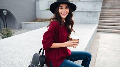 Mulher sentada sorrindo segurando café