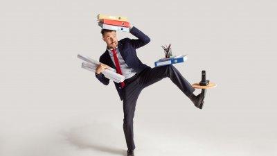 Homem se esforçando para equilibrar varias coisas com as mãos, os pés e a cabeça