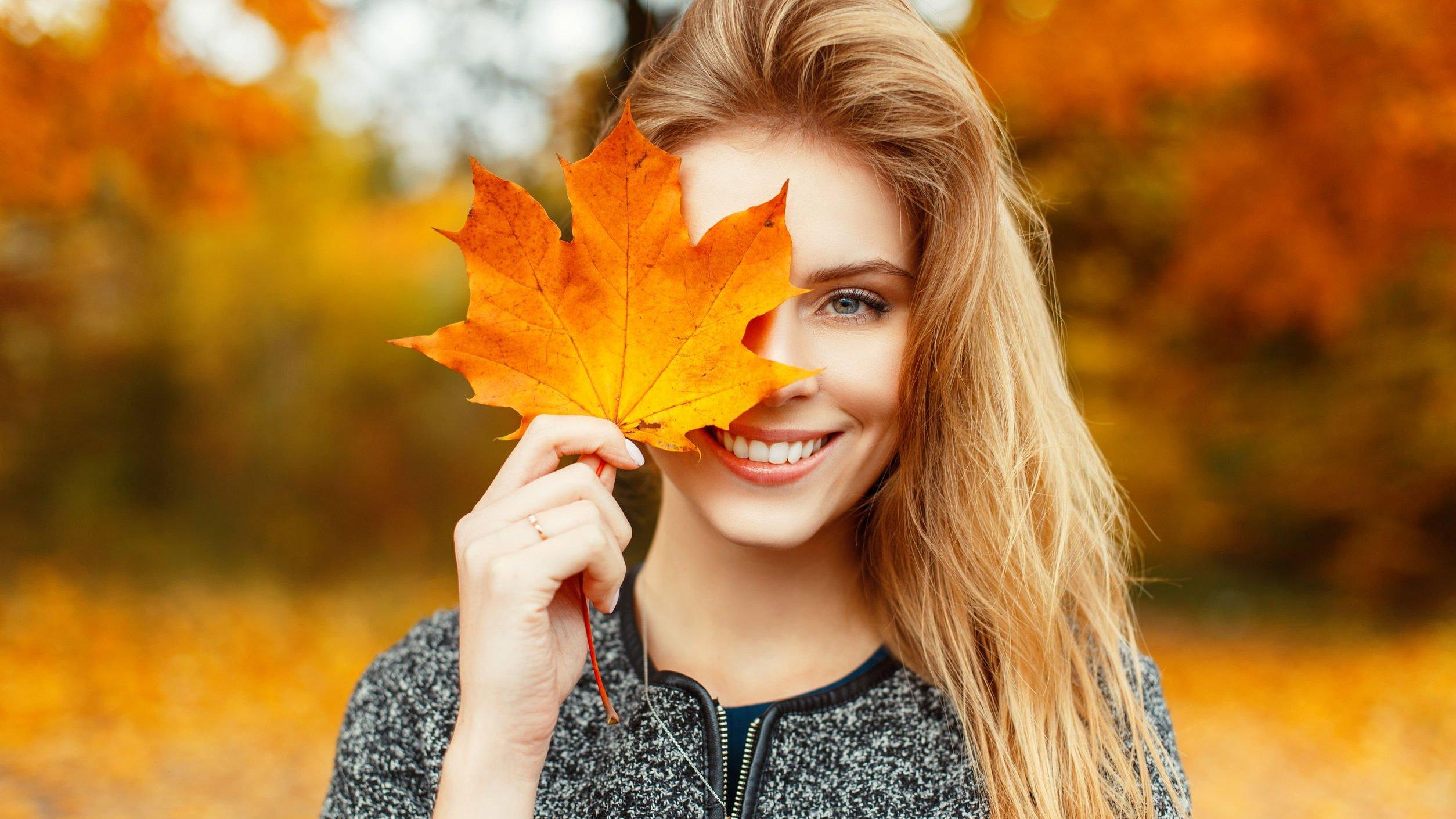 Mulher tampando o olho com folha de árvore e sorrindo