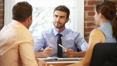 Casal conversando com homem em escritório