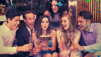 Pessoas comemorando aniversário ao redor de bolo com velas acesas