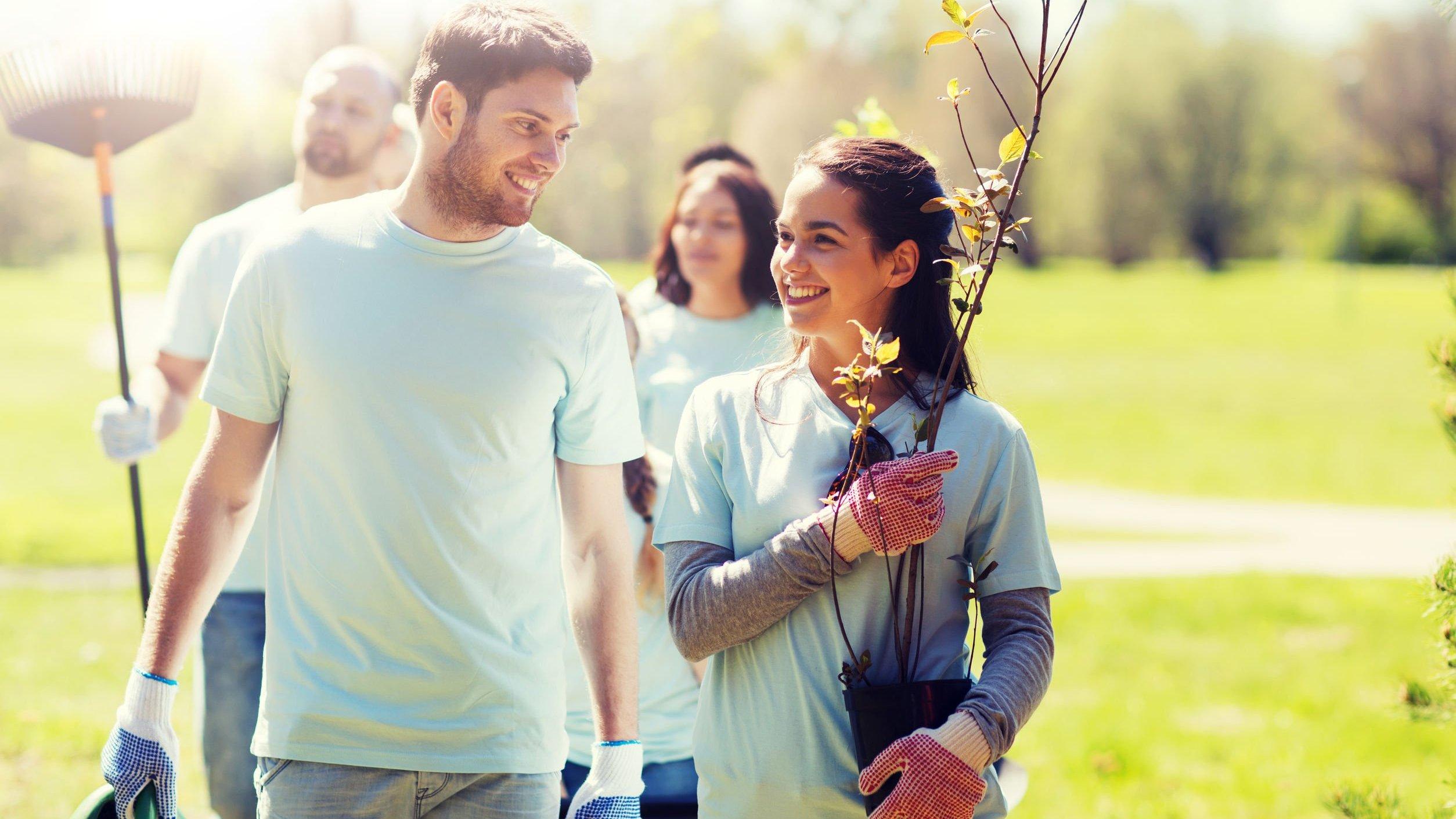 Homem e mulher olhando um para outro sorrindo enquanto caminham segurando mudas de árvores