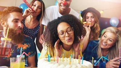 Pessoas cantando parabéns e mulher assoprando velinha acessa em cima de bolo de aniversário