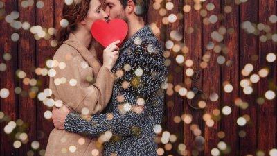 Casal se beijando e mulher segurando papel em formato de coração