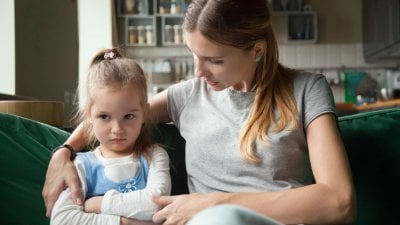 Mãe e filha sentadas em sofá conversando