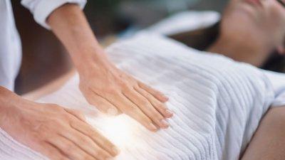 Homem com as mãos sobre mulher deitada em maca