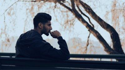 Homem pensativo sentado em um banco de praça