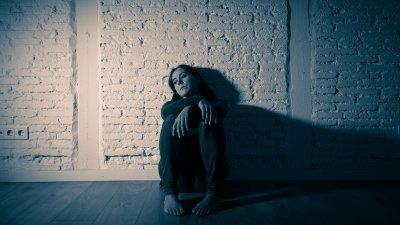 Mulher sentada triste, apoiando-se em parede de tijolos