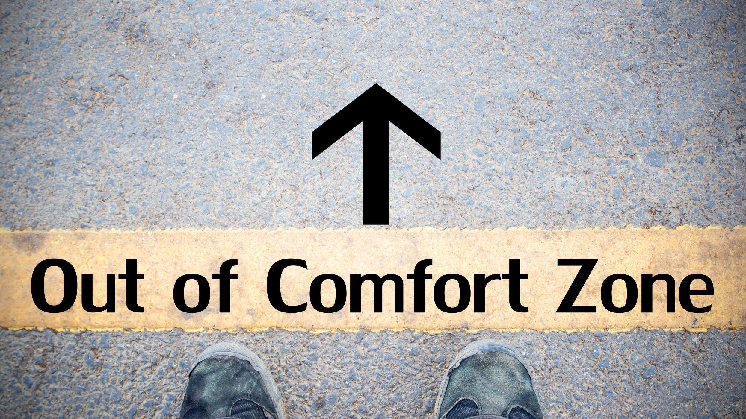 Pernas e sapato de homem atrás de faixa escrito fora da zona de conforto em inglês com seta apontando para frente