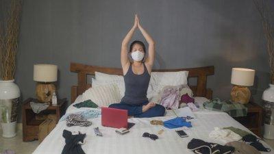 Mulher em casa usando máscara com coisas espalhadas na cama
