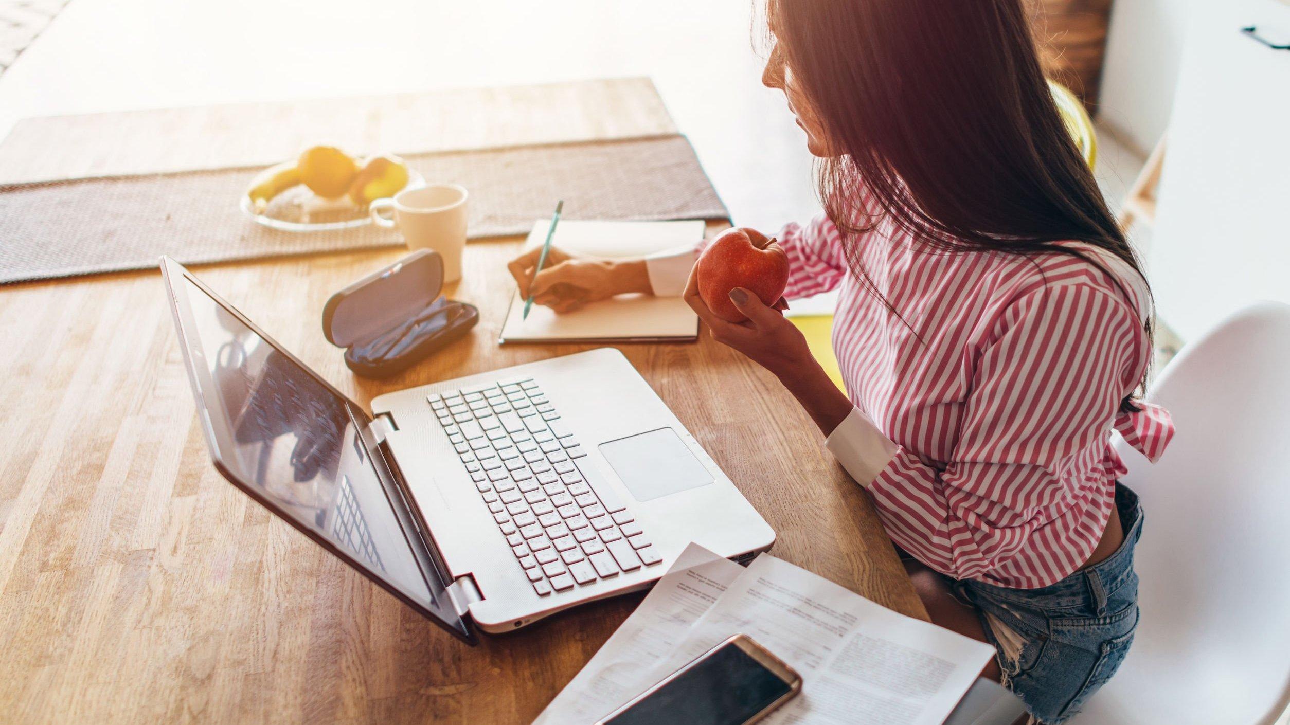 Mulher trabalhando em computador na mesa de casa e comendo maça