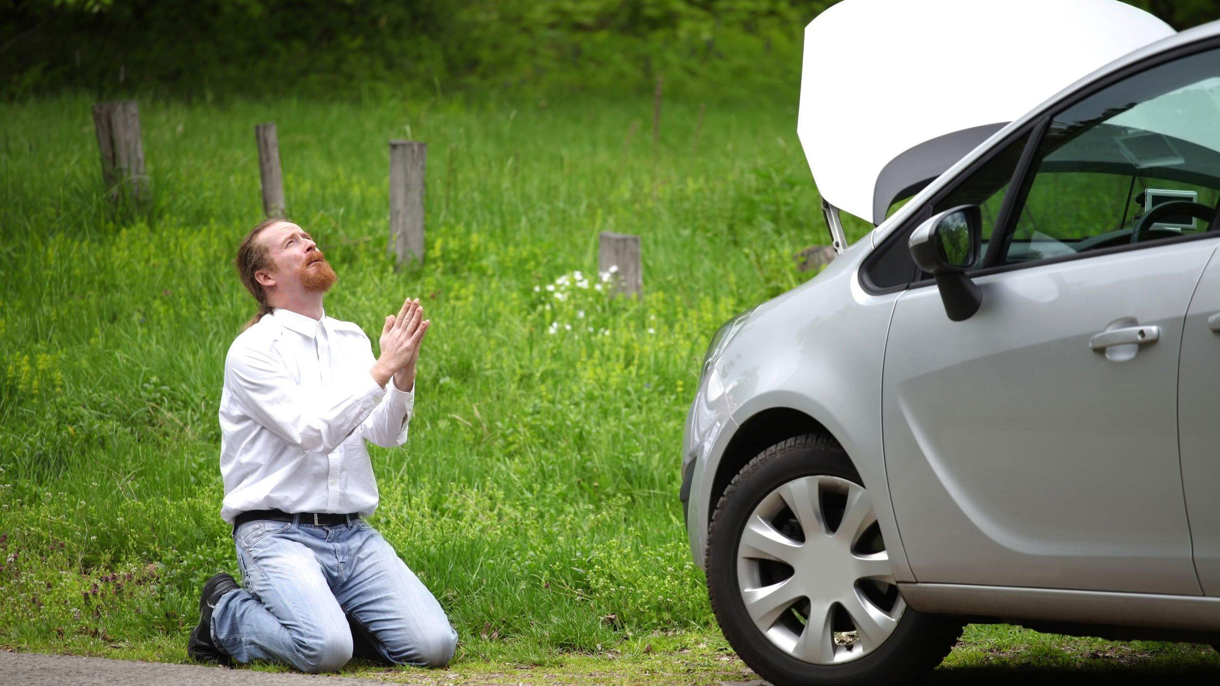 Homem ajoelhado orando em frente a carro quebrado na estrada