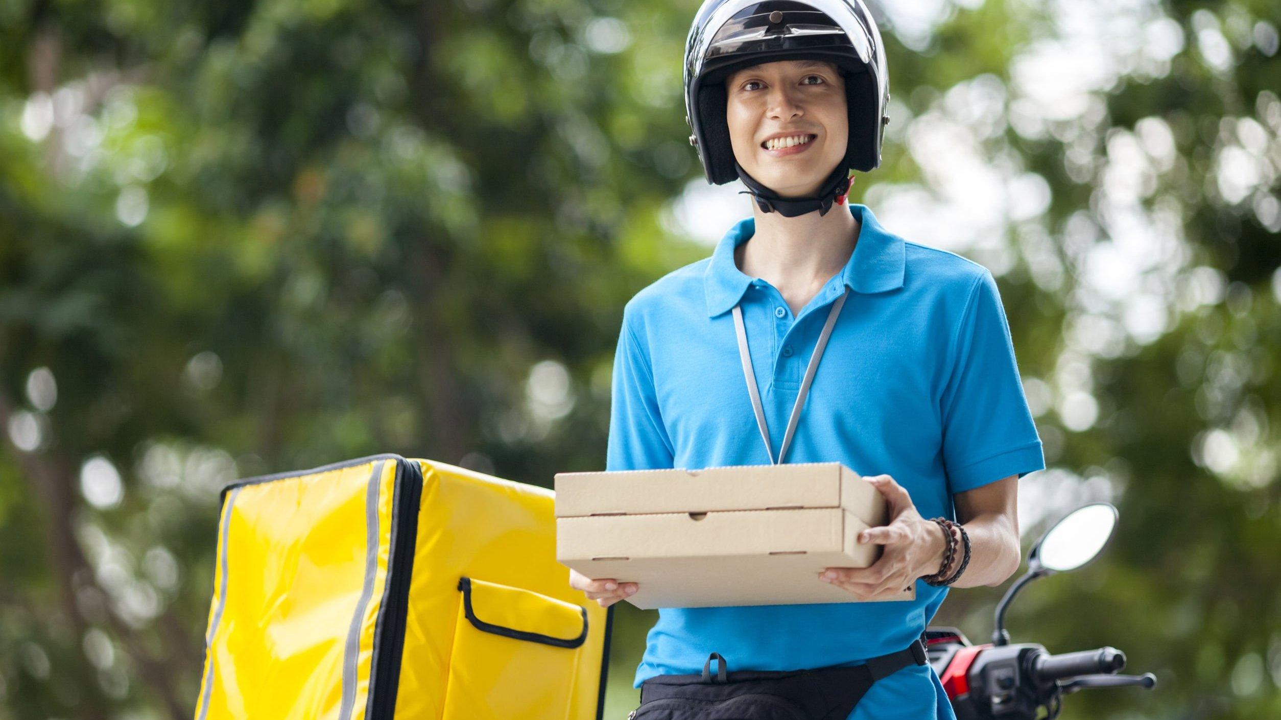 Homem segurando caixas de pizza em pé ao lado de moto, sorrindo