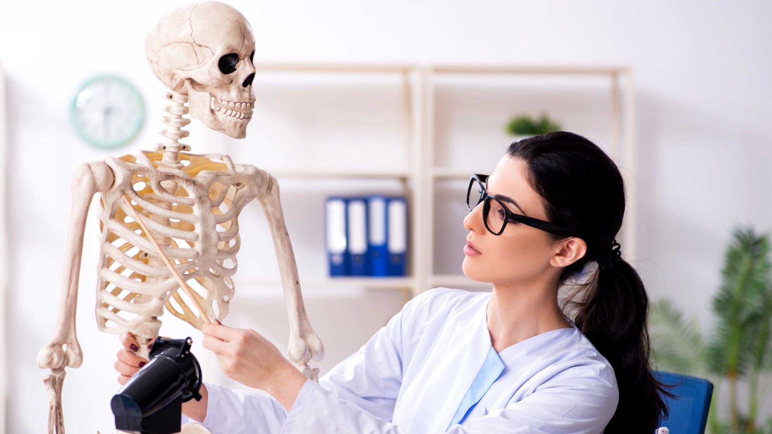 Mulher mexendo em esqueleto com palito