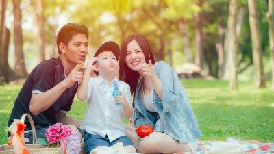 Família reunida sentada em toalha de pique nique, em parque durante dia ensolarado.