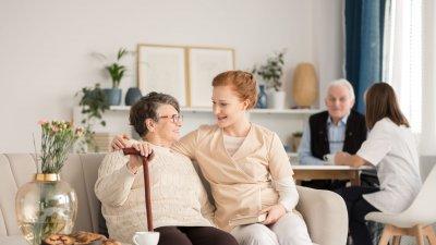 Senhora e mulher sentadas em sofá, sorrindo e conversando