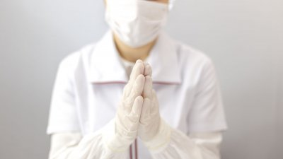 Enfermeiro usando equipamento de proteção, com as mãos juntas orando
