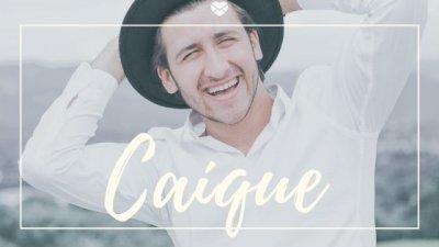 Nome Caíque escrito em branco sobre foto de homem jovem, com chapéu, ao ar livre, dando risada.
