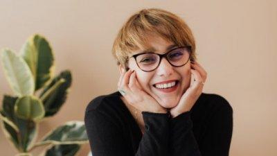 Mulher sorrindo fazendo sinal de joia com as mãos