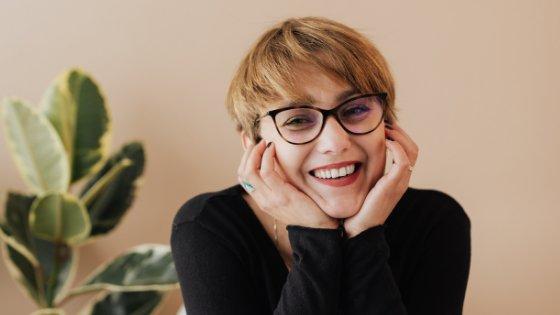 Mulher sorrindo apoiando suas mãos no rosto