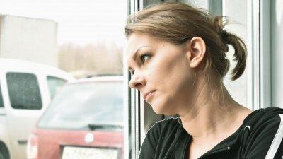 Mulher olhando pela janela com expressão de saudade