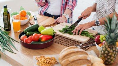 Pessoas cortando alimentos para cozinhar