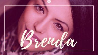 Nome Brenda escrito em branco sobre foto de close em rosto de mulher jovem sorrindo disfarçadamente.