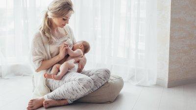 Mulher amamentando bebê sentada em almofada no chão