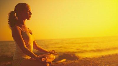 Mulher sentada de pernas cruzadas e olhos fechados meditando na praia