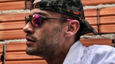 Homem de boné usando óculos em frente de parede de tijolos sem reboco
