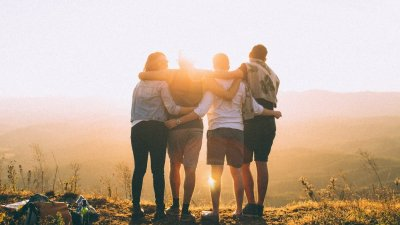 Amigos abraçados olhando por do sol