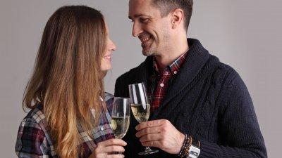 Homem e mulher sorrindo, brindando com taças de champanhe