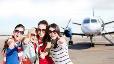 Amigas reunidos sorrindo em frente à avião