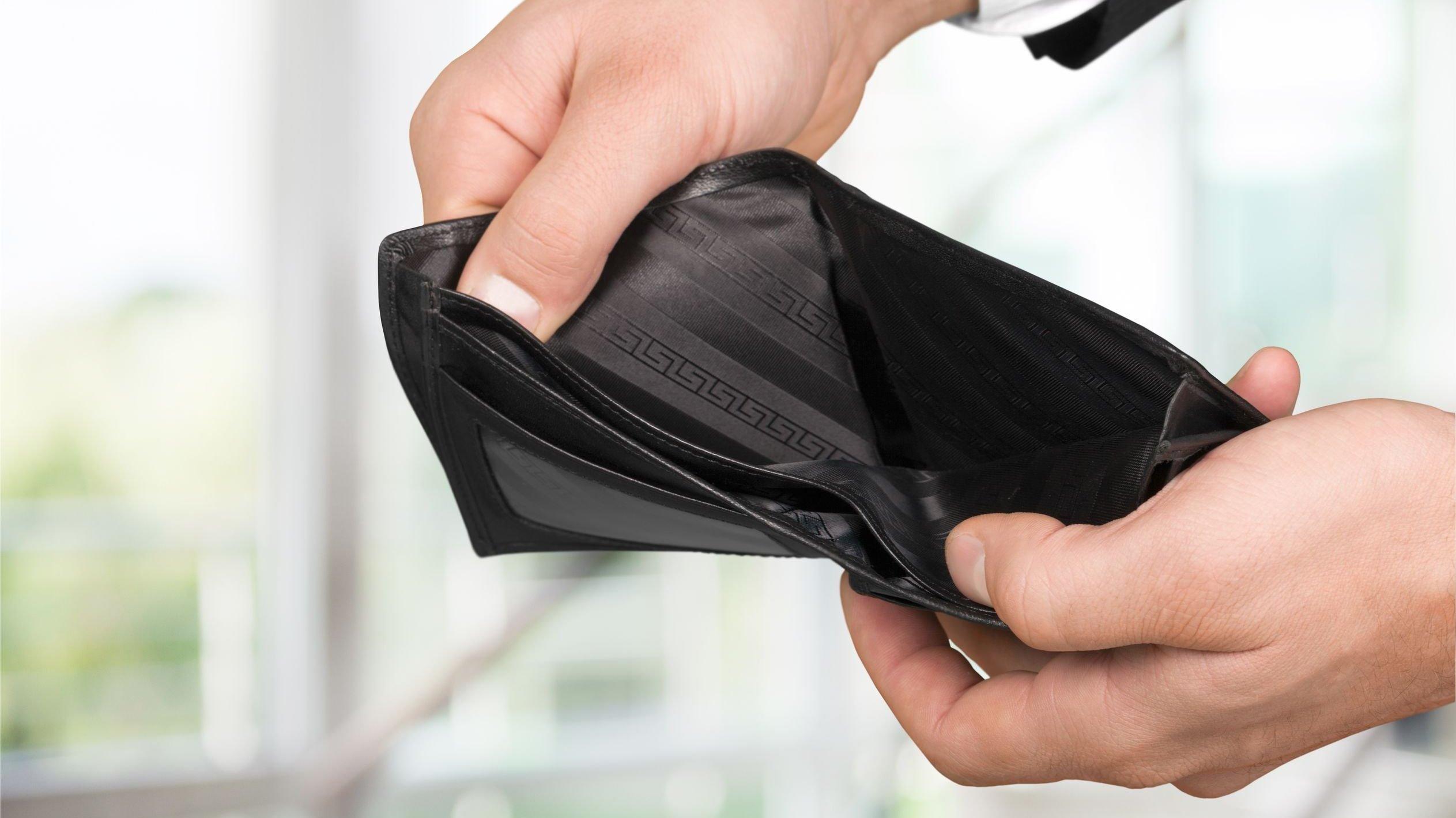 Pessoa mostrando carteira sem dinheiro