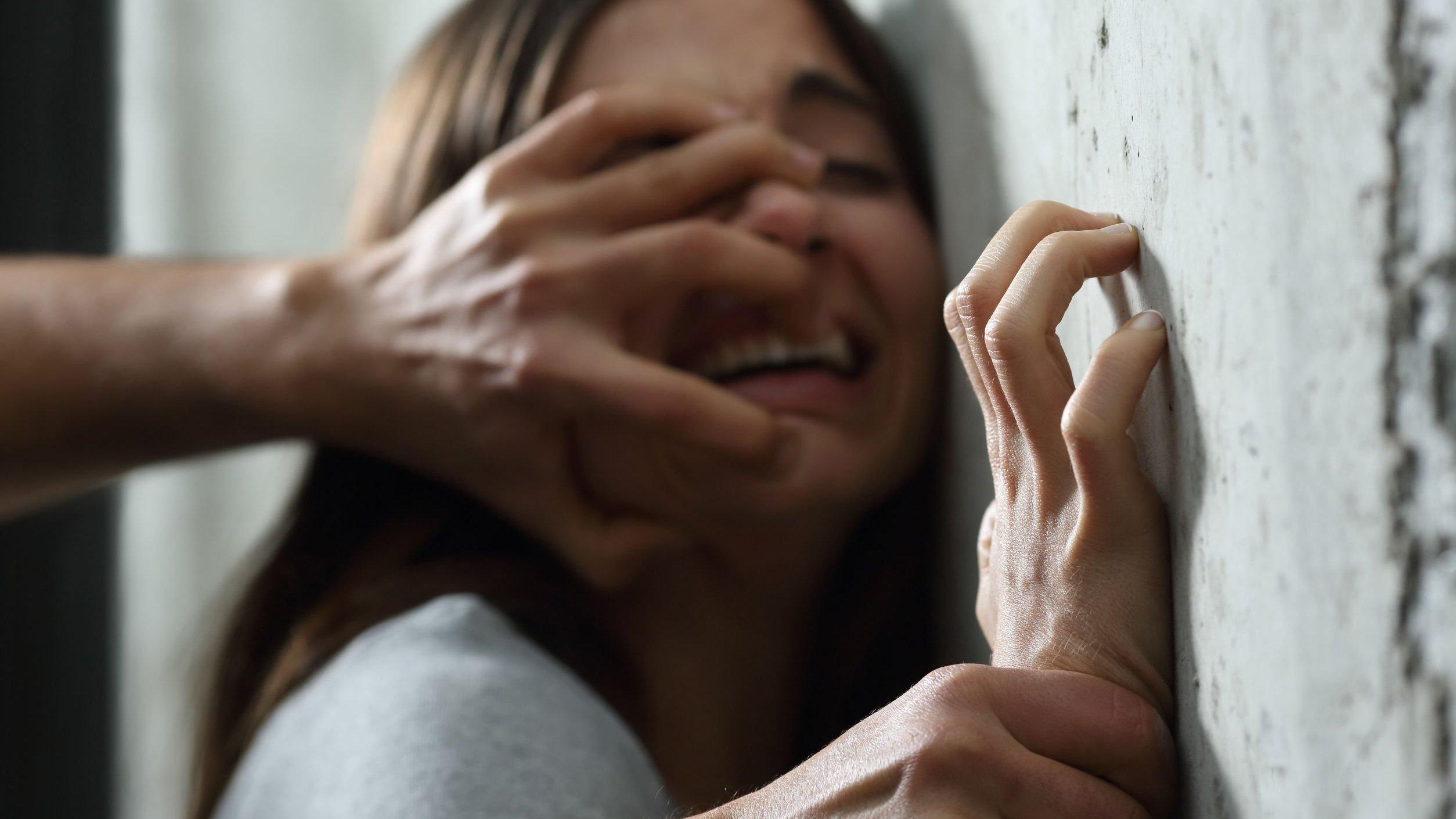 Mão de homem empurrando rosto de mulher chorando contra parede