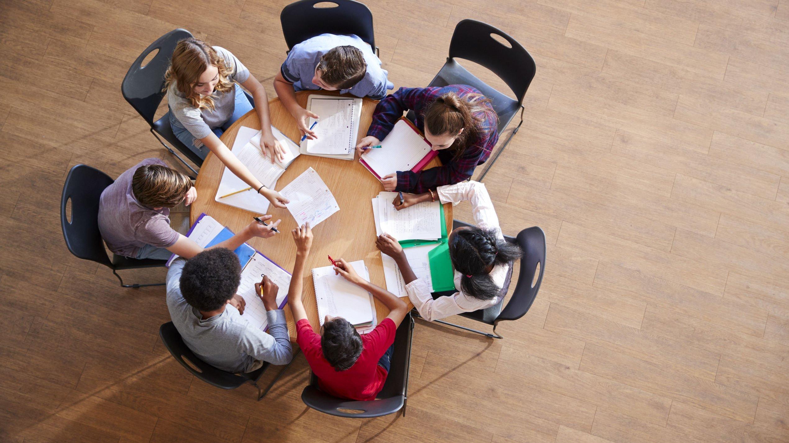 Grupo de estudantes reunidos sentados fazendo trabalho