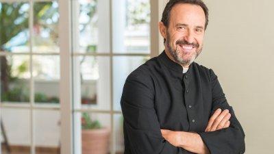 Padre de braços cruzados sorrindo em igreja