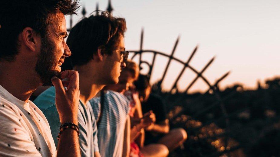 Amigos sentados em laje de casa observando por do sol