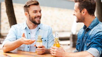 Homens conversando bebendo cerveja sentados em mesa de restaurante