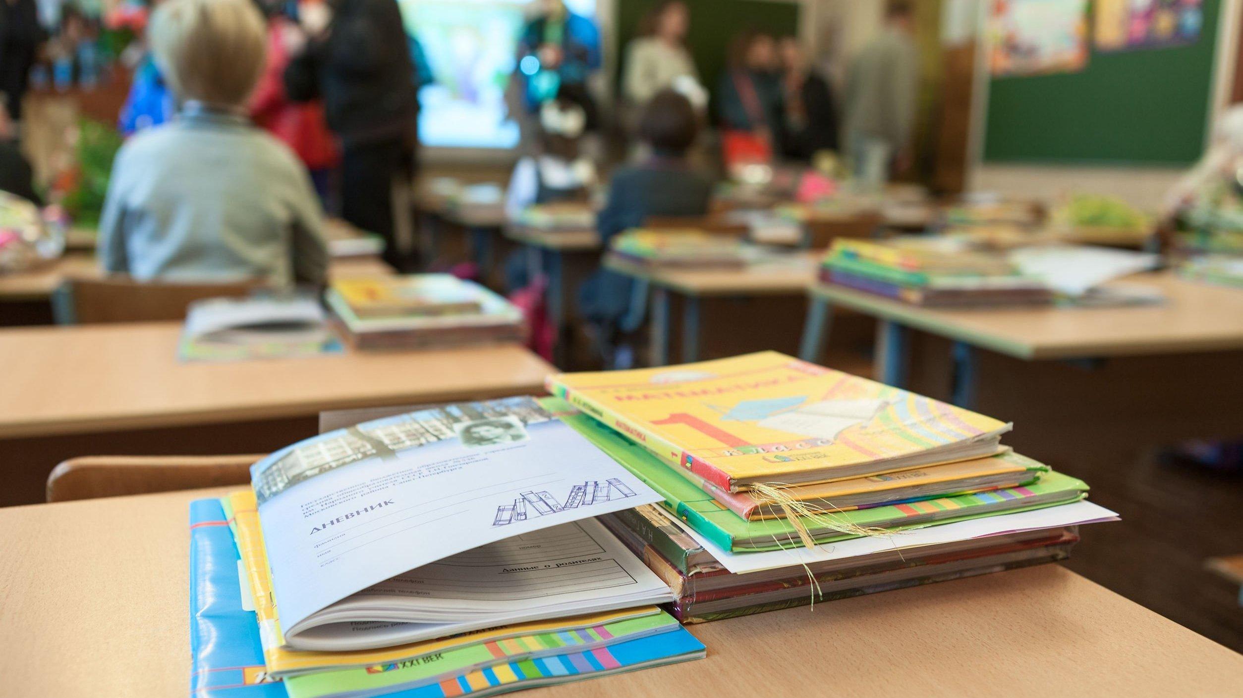 Livros em cima de carteiras de escola