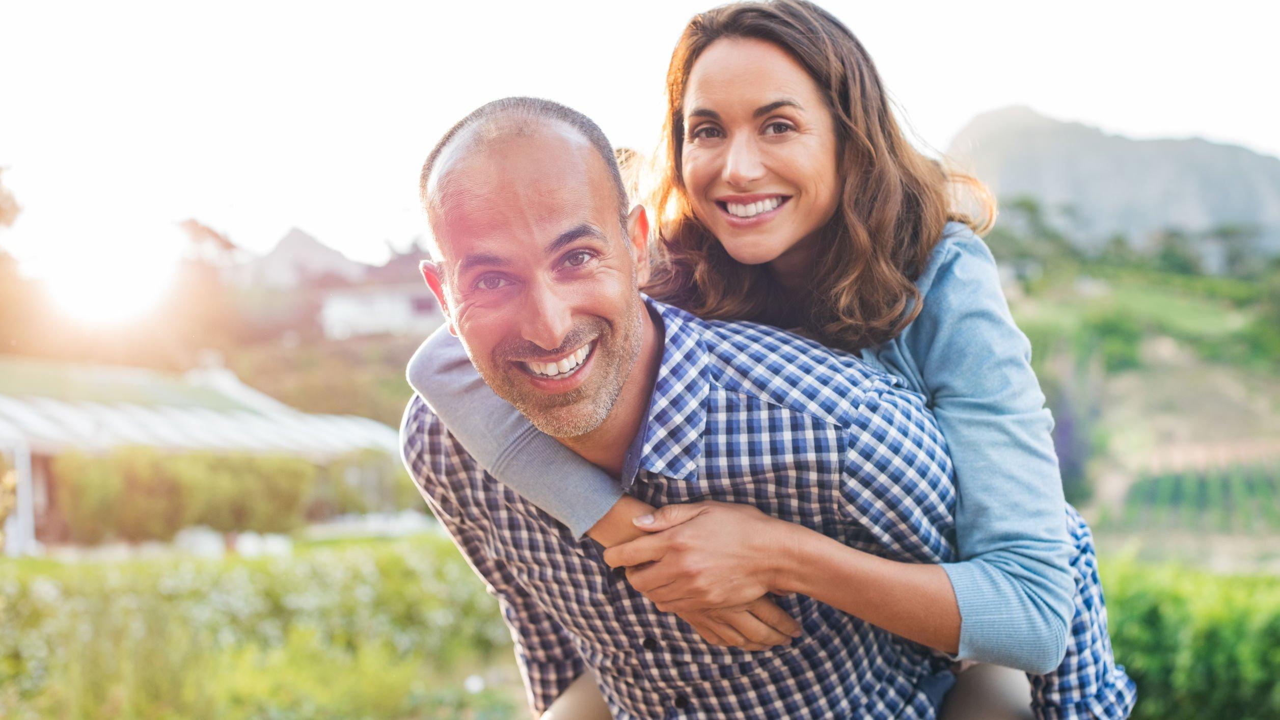 Homem segurando mulher nas costas, os dois estão sorrindo em um campo durante um dia ensolarado