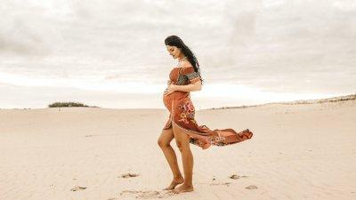 Mulher grávida passando a mão em barriga