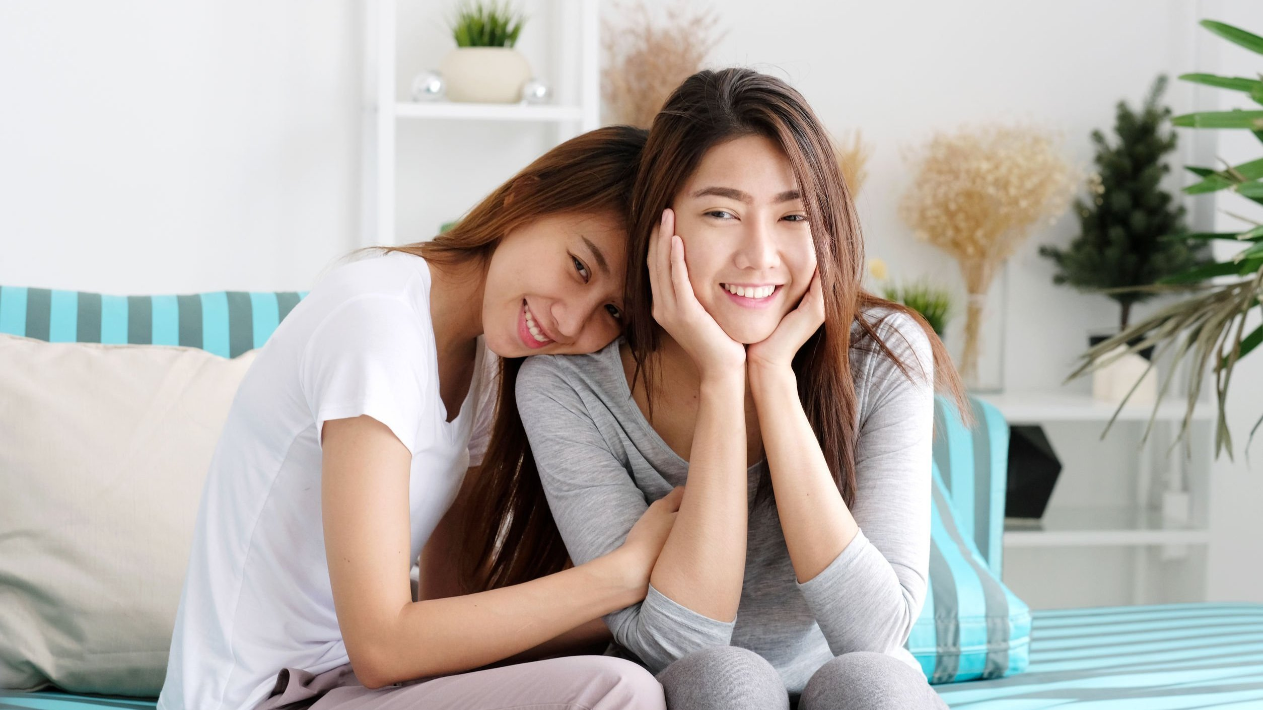 Amigas sorrindo e se abraçando, ambas sentadas em sofá