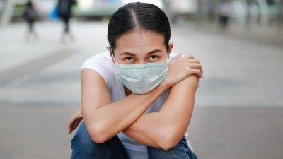 Mulher sentada com máscara e olhos abertos abraçando os joelhos