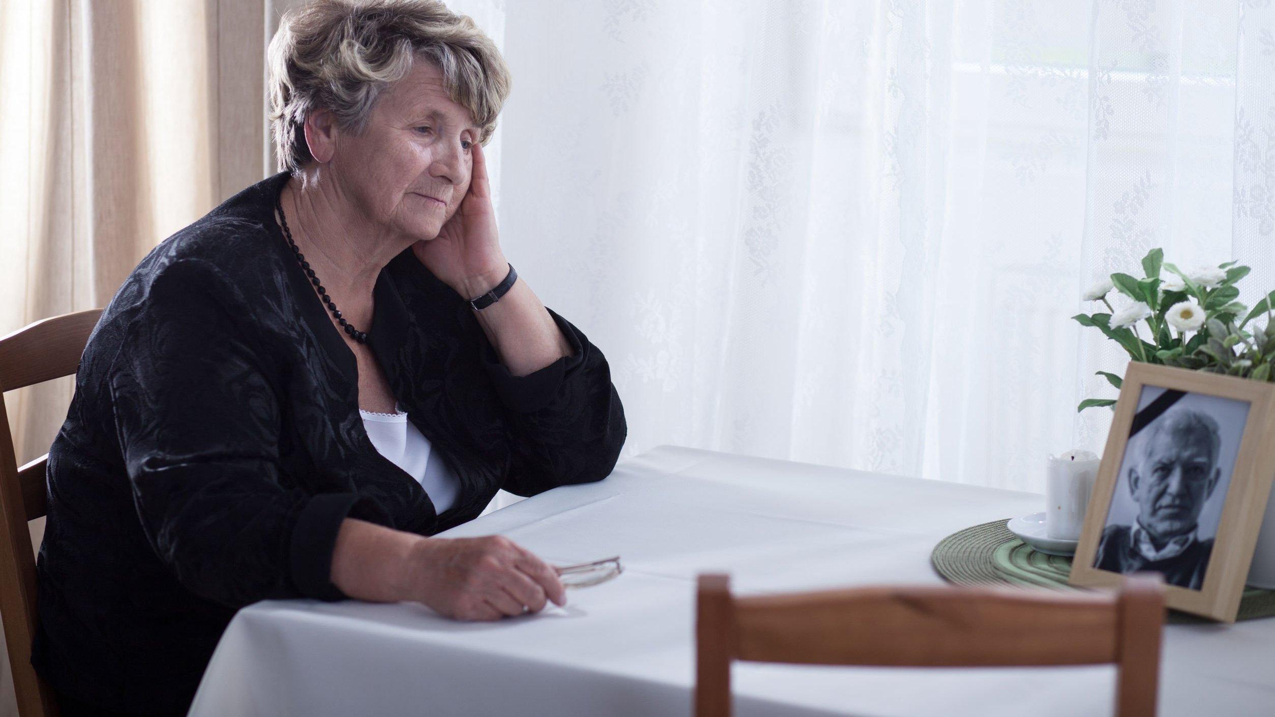 Senhora de idade sentada em mesa observando foto de homem falecido