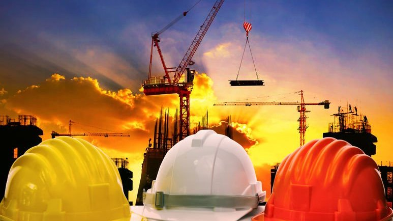 Foto de capacetes de engenheiros civis. Ao fundo, uma obra.