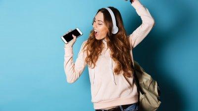 Mulher usando fones, ouvindo música, segurando celular e cantando com a mão pra cima.