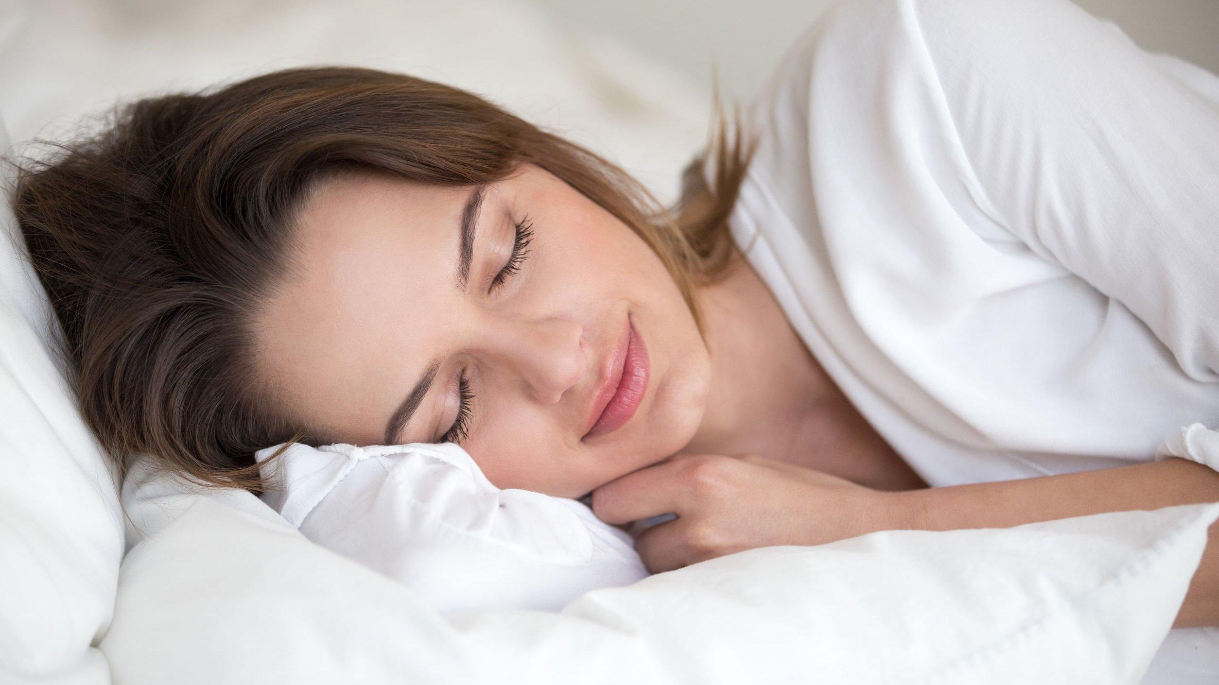 Mulher dormindo em travesseiro branco